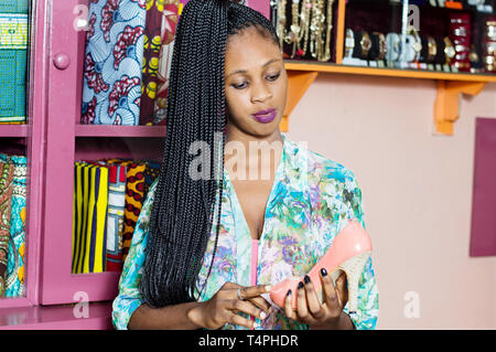 Young woman holding a shoe looks at her carefully before buying it. - Stock Image
