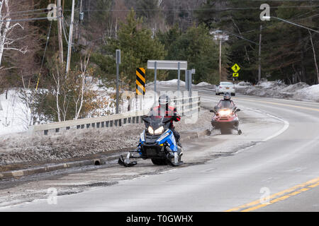 Two snowmobiles riding along the edge of a road in Speculator, NY USA between snow covered trails. - Stock Image