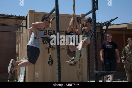 UFC athletes from left, Jake Ellenberger, Diego Sanchez, and Emily Miller, exercise while visiting U.S. Army Paratroopers at Camp Swift, Iraq, June 5, 2017. The athletes participated in the Pro Sports MVP MMA Cage Crusader Tour and visited service members deployed in support of Combined Joint Task Force-Operation Inherent Resolve. CJTF-OIR is the global Coalition to defeat ISIS in Iraq and Syria. (U.S. Army photo by Cpl. Rachel Diehm) - Stock Image