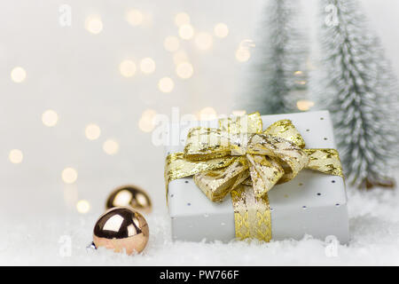 Small elegant silver gift box tied with golden ribbon bow baubles in winter scene in forest with fir trees snow. Christmas New Years presents holiday  - Stock Image
