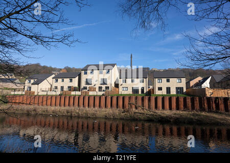 New houses with flood defence barrier along the River Calder, Copley, West Yorkshire - Stock Image