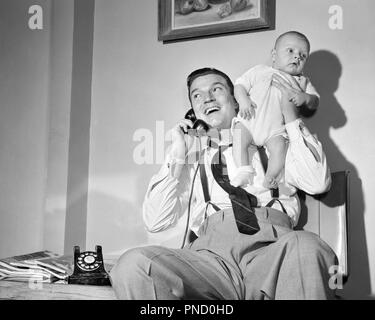 1940s 1950s MAN FATHER TALKING ON TELEPHONE HOLDING BABY BOY UP WITH ONE HAND - b809 DEB001 HARS INFANT SONS JOY LIFESTYLE HOME LIFE COMMUNICATING COPY SPACE FULL-LENGTH HALF-LENGTH PERSONS MALES FATHERS B&W DADS LOW ANGLE PRIDE UP NECKTIE PHONES SUSPENDERS CONNECTION TELEPHONES SUPPORT DEB001 BABY BOY COOPERATION JUVENILES MID-ADULT MID-ADULT MAN BLACK AND WHITE CAUCASIAN ETHNICITY OLD FASHIONED - Stock Image