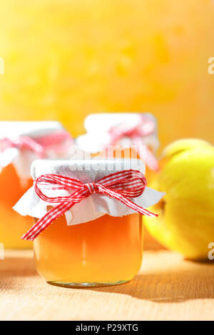 Quince jelly in glass jars with quinces on a wooden table in bright sunshine in front of an yellow and orange background, copy space. - Stock Image