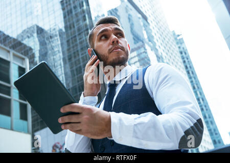 Businessman with tablet computer speaks by phone in big city - Stock Image