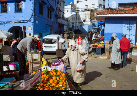 Chefchaouen, Morocco : A senior Moroccan man wearing a djellaba  shops for fruit and vegetables at Plaza Bab Suk market square, in the blue-washed med - Stock Image
