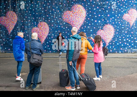 People watching a woman posing against a large colourful mural painted on a wall in London. - Stock Image