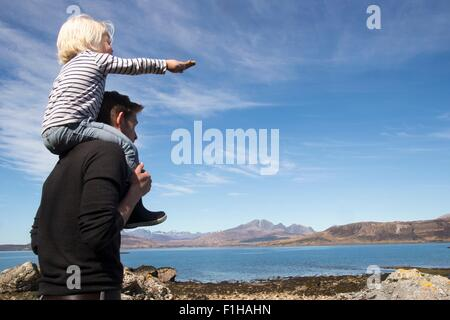 Father carrying son on shoulders, Loch Eishort, Isle of Skye, Hebrides, Scotland - Stock Image