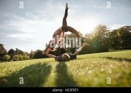 Outdoor shot of young man and woman doing yoga in pair. Couple doing acrobatic yoga exercise at park. - Stock Image