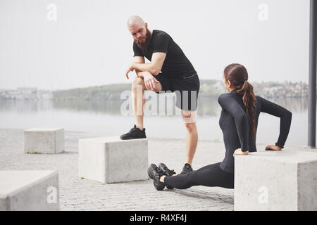 Fitness couple stretching outdoors in park near the water. Young bearded man and woman exercising together in morning - Stock Image