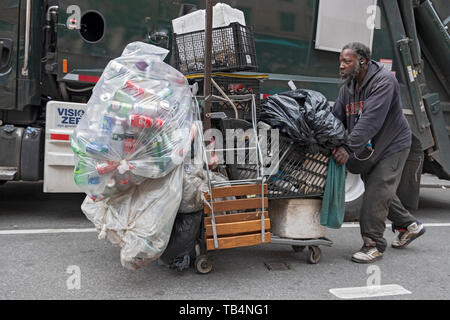 A man who collects empty deposit bottles pushing a supermarket cart down Broadway in Manhattan, New York City. - Stock Image