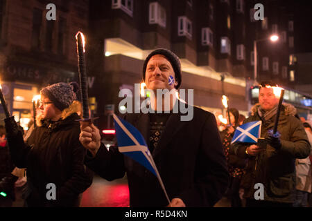 Glasgow, Scotland, UK. 30th Nov, 2018. Glasgow's West End Festival's third torchlight St Andrew's Day parade started in the dry at Glasgow's Botanic Gardens. A later very heavy shower may have extinguished a few torches but didn't dampen spirits as the parade made it's way through Glasgow's West End to Kelvingrove Art Gallery and Museum Credit: Kay Roxby/Alamy Live News - Stock Image