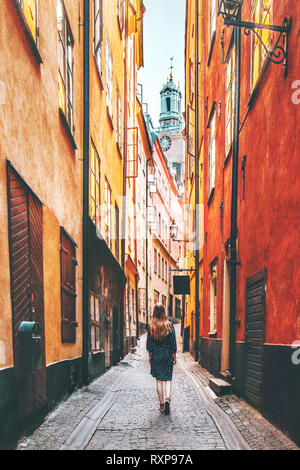 Woman tourist walking alone in Stockholm narrow street traveling lifestyle summer vacations in Sweden - Stock Image