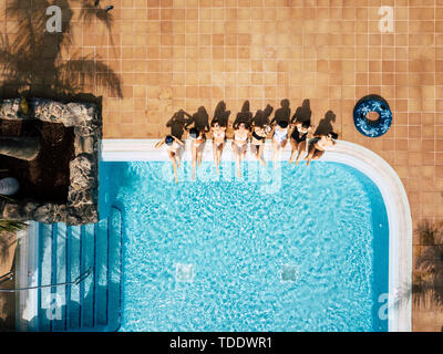 Friends females caucasian people enjoying the swimming pool in summer holiday vacation at hotel or resort - high top vertical view of young women sit  - Stock Image