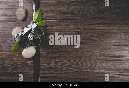 Photographers business card background. Zen photography background concept with green leaves and sea stones on dark brown natural wooden background. - Stock Image
