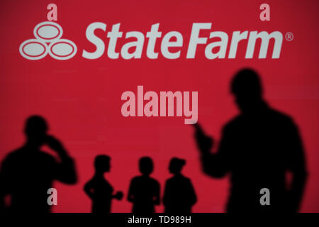 The State Farm logo is seen on an LED screen in the background while a silhouetted person uses a smartphone in the foreground (Editorial use only) - Stock Image