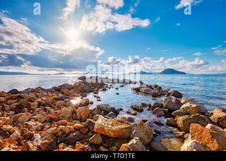 Beautiful coastal sunset with breakwater groynes in the foreground on the Aegean sea in Turgutreis Bodrum Mugla Turkey - Stock Image