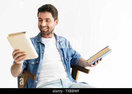 Portrait of a handsome bearded man wearing casual clothes sitting in chair isolated over white background, holding books - Stock Image