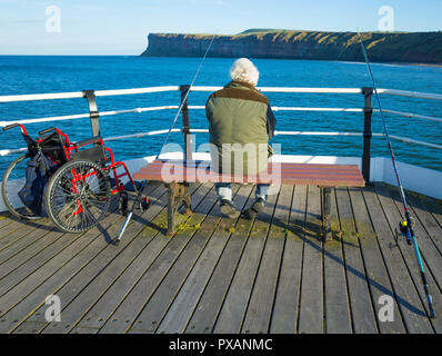 A disabled elderly angler  with two fishing rods and his wheel chair fishing from a seat on Saltburn Pier North Yorkshire on a fine autumn day - Stock Image