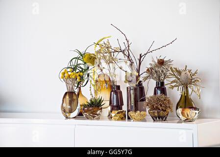 Flower vases on sideboard at modern home - Stock Image