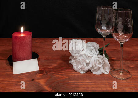 Beautiful etched wine glasses with awhite roses and red candle and name tag on wooden table and dark background. Valentines, Mothers Day, Easter, Chri - Stock Image