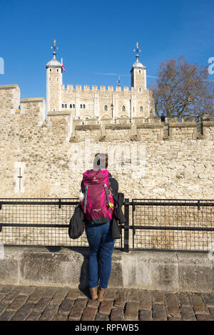 Girl tourist wearing a purple backpack rucksack leaning on a fence looking at the white tower part of the tower of London England with blue sky - Stock Image