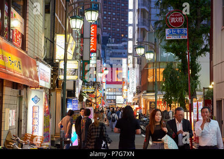 Night shot of busy street in the area of Shinjuku, central Tokyo, Japan. - Stock Image