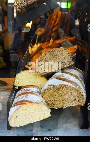 Display window of a bakery and pastry shop. Assortment of different kinds of freshly baked artisan bread rye whole wheat bran loaves. Authentic urban  - Stock Image