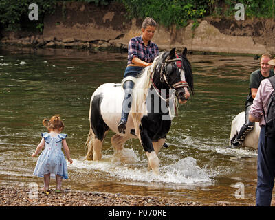 little girl watching female traveller riding horse out of the water after washing it in the River Eden, Appleby-in Westmorland at the crowded annual Appleby Horsefair, Cumbria,England UK, 8 June, 2018. little girl watching horse in the River Eden Credit: Steve Holroyd/Alamy Live News - Stock Image