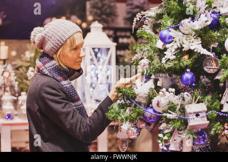 people at christmas market, woman choosing festive decoration in the shop - Stock Image