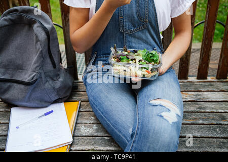 Midsection portrait of a student girl sitting in a bench while eating healthy salad with pasta in a glass lunch box - Stock Image