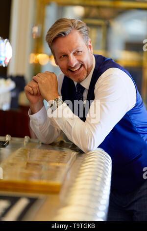 Man smiling at a bar - Stock Image
