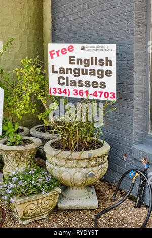 English language classes sign in a flower pot near a busy sidewalk in Prattville Alabama, USA. - Stock Image