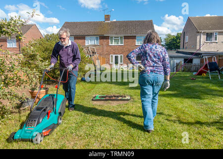 A retired couple doing gardening in a residential back garden on a sunny day with blue sky. The man mows the lawn with an electric lawnmower. - Stock Image