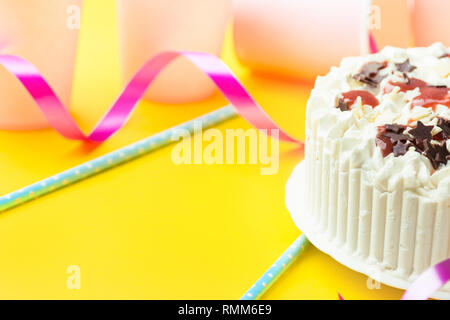 Sponge layer birthday cake with whipped cream frosting chocolate star sprinkles strawberry jam. Pink paper drinking cups blue straws curly ribbon on y - Stock Image