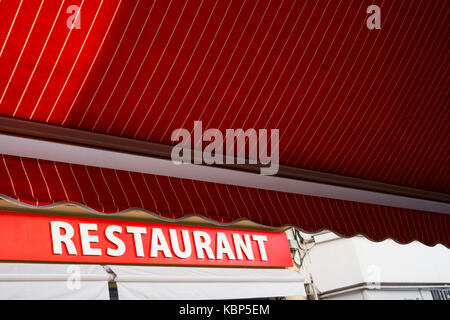 A red canopy opposite a red restaurant sign in Lloret de Mar, Spain - Stock Image