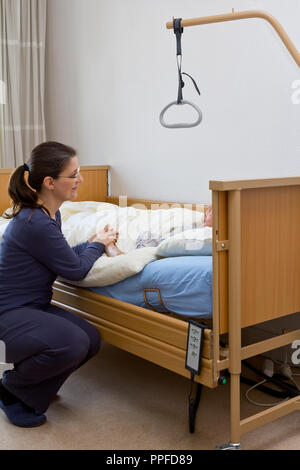 Woman at the nursing bed of her terminally ill grandmother, holding her hand and talking to her. Concept of dying at home or in a hospice. - Stock Image