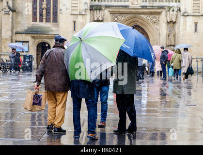 Bath, UK. 8th February, 2019. As storm Eric brings gales and heavy rain across the UK pedestrians are pictured outside Bath Abbey carrying umbrellas as they braves the heavy rain and wind. Credit: Lynchpics/Alamy Live News - Stock Image