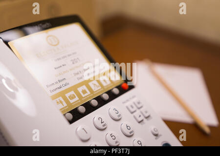 A closeup of a white telephone in a hotel room with an out of focus notepad in the background. Electra Palace, Thessaloniki, Greece - Stock Image