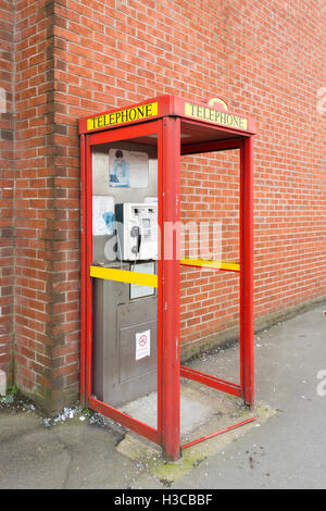 Modern utilitarian urban UK telephone kiosk is poor state due to vandalism. All glass panels have been broken and - Stock Image