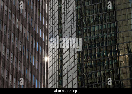 Sun reflection on an abstract financial skyscraper facade with mirror glass in a typical North American CBD, or Center Business District, taken at daw - Stock Image