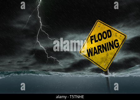 Flood Warning sign submerged in rising water against a stormy background with rain and lightning. Dirty and angled sign adds to the drama. - Stock Image