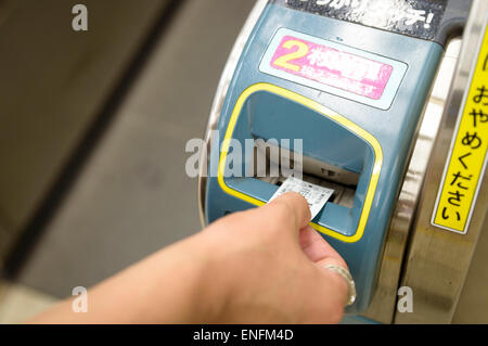 Hand inserting train ticket into ticket gate/turnstile in Japan. Japanese automation. - Stock Image