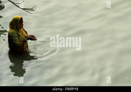 Indian woman praying at the ghats of Hoogli river, Kolkatta, India - Stock Image