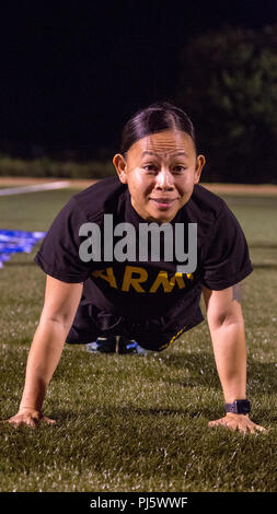 U.S. Army Drill Sgt. Lyra Lebron-Brown, a competitor in the Drill Sergeant Of The Year Competition, completes the push-up event of the Army Physical Fitness Test at Hellcat Field on Fort Sill, OK., Aug. 27, 2018. The Drill Sergeant Of The Year Competition is one of the most physically demanding and mentally tough challenges any Soldier can face in a U.S. Army competition. (U.S. Army photo by Pfc. Joshua Hugley) - Stock Image