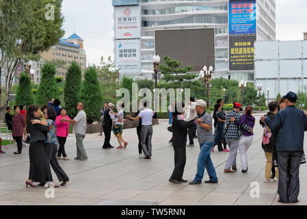 People dancing in the square, Zhangye, Gansu Province, China - Stock Image