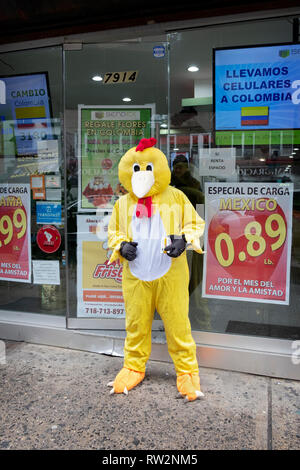 A Latin American man dressed as a chicken hands out leaflets outside of Casablalnca Group, a place to exchange foreign currency in Jackson Heights. - Stock Image