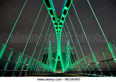 Modern steel bridge lit with changing coloured lights at night. - Stock Image