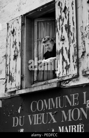 Paris France, Woman  leans out of a window with shutters, 1994 - Stock Image