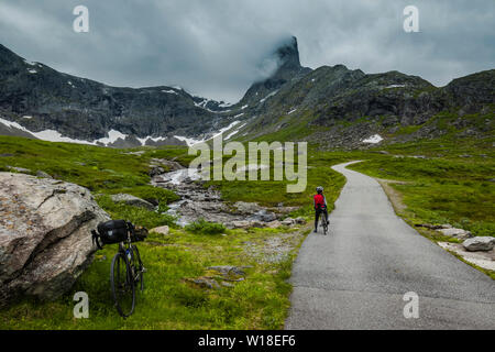 Female cyclist on private toll road through Vengedalen, close to Andalsnes, Norway. - Stock Image