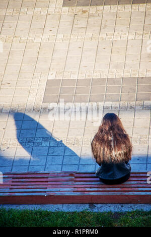 lonely girl sits on a bench waiting for happiness and love - Stock Image